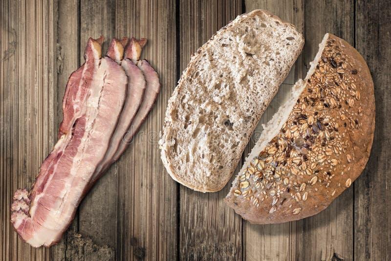 Pão integral com as fatias de toucinho do bacon no fundo de madeira velho fotos de stock