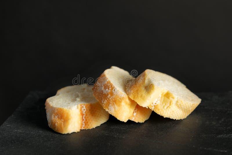 Pão integral cortado saboroso no preto imagens de stock