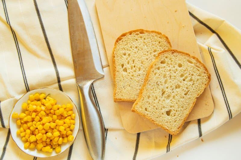 Pão integral, grões do milho e faca tradicionais recentemente cozidos na toalha de cozinha de linho, configuração lisa imagem de stock royalty free