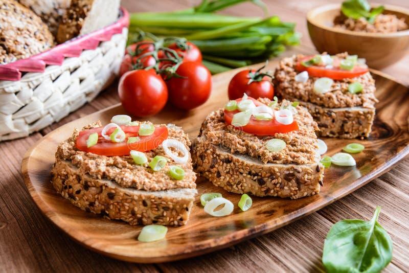 Pão integral inteiro com propagação, tomate e cebola dos peixes fotografia de stock royalty free