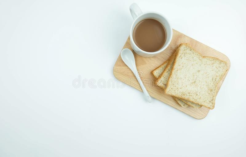 Pão integral inteiro cortado e uma xícara de café em desbastar a madeira sobre foto de stock