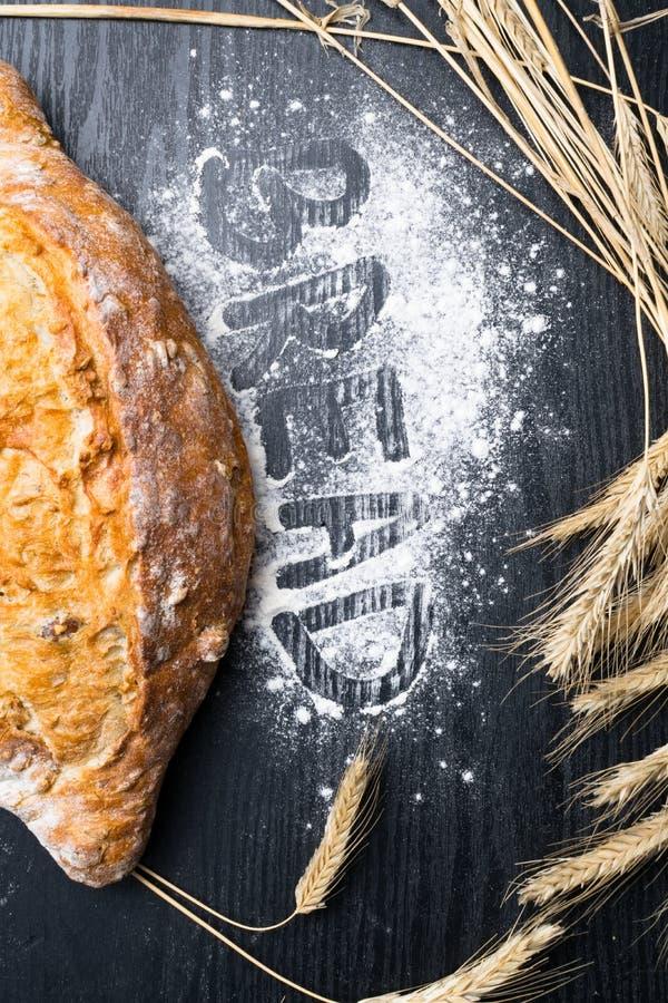 Pão integral ou naco inteiro fresco e delicioso na tabela de madeira para o fundo da dieta saudável com inscrição imagem de stock