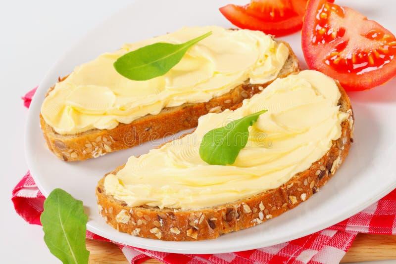 Pão inteiro da grão com manteiga foto de stock royalty free