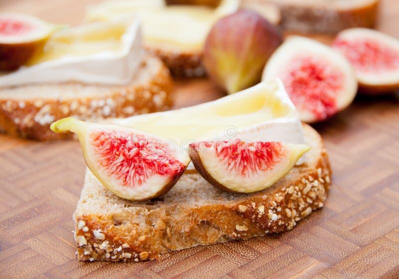 Pão inteiro da grão com queijo e os figos derretidos do brie. foto de stock