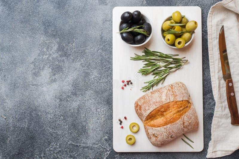 Pão italiano do ciabatta com azeitonas e alecrins em uma placa de corte Fundo concreto escuro Copie o espa?o imagens de stock