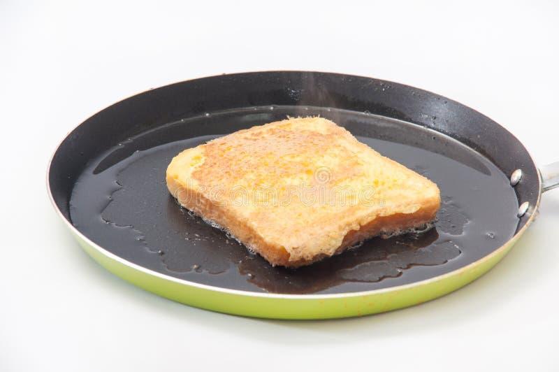 Pão mergulhado no ovo e colocado no óleo quente em uma frigideira fotos de stock royalty free