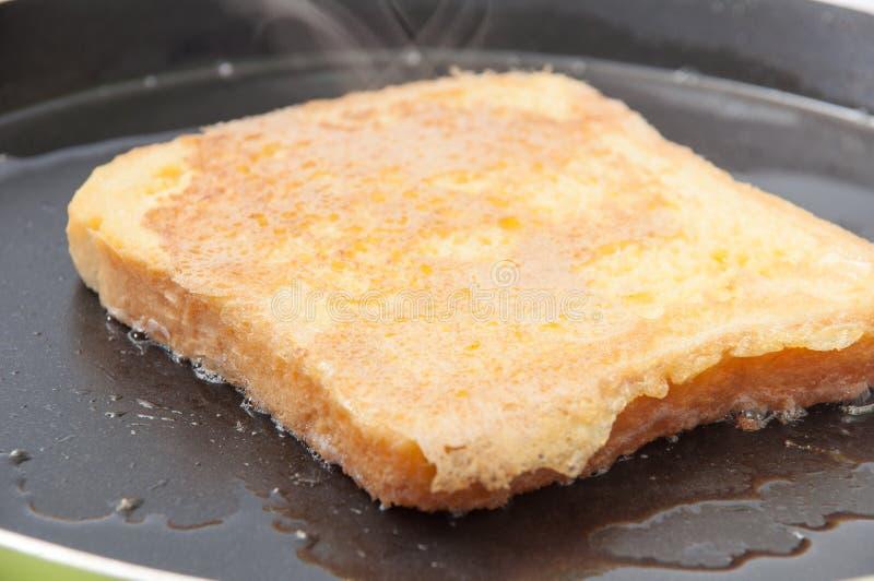 Pão mergulhado no ovo e colocado no óleo quente em uma frigideira imagem de stock royalty free