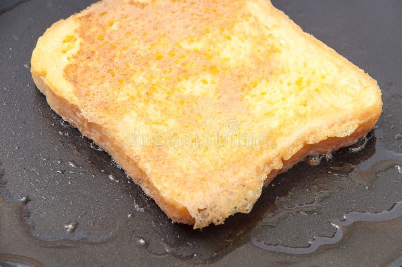 Pão mergulhado no ovo e colocado no óleo quente em uma frigideira foto de stock royalty free