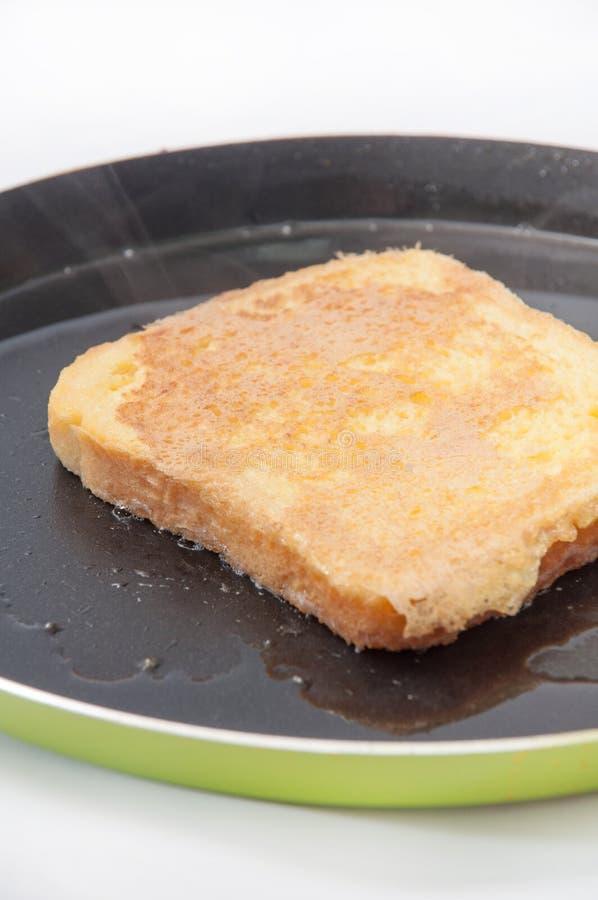 Pão mergulhado no ovo e colocado no óleo quente em uma frigideira imagens de stock royalty free