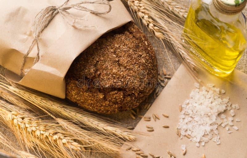 Pão, orelhas, grões e óleo vegetal no pano de saco fotos de stock