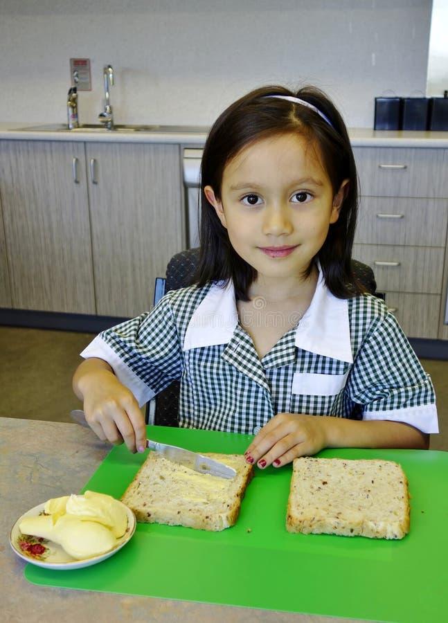 Pão pondo manteiga da menina nova da escola. foto de stock royalty free