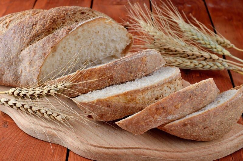 Pão preto cortado em uma placa de corte, orelhas do trigo foto de stock