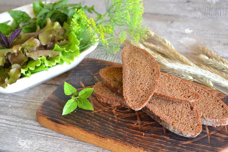 Pão rústico nas fatias em uma tabela de madeira do vintage velho no estilo gasto imagens de stock