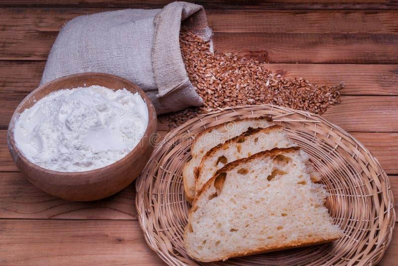 Pão recentemente caseiro e farinha em grões da bacia e do trigo no saco na tabela de madeira fotografia de stock