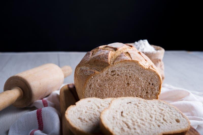 Pão recentemente cozido na placa de corte de madeira foto de stock