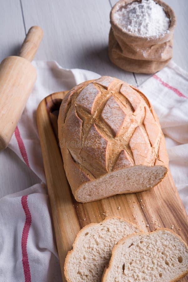 Pão recentemente cozido na placa de corte de madeira fotografia de stock