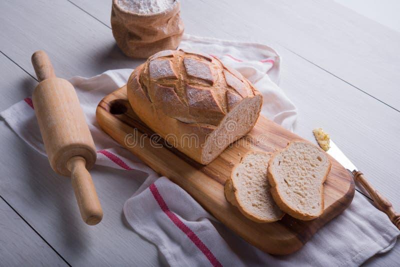 Pão recentemente cozido na placa de corte de madeira imagem de stock royalty free