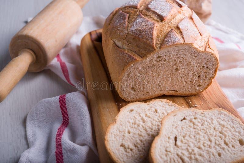 Pão recentemente cozido na placa de corte de madeira foto de stock royalty free