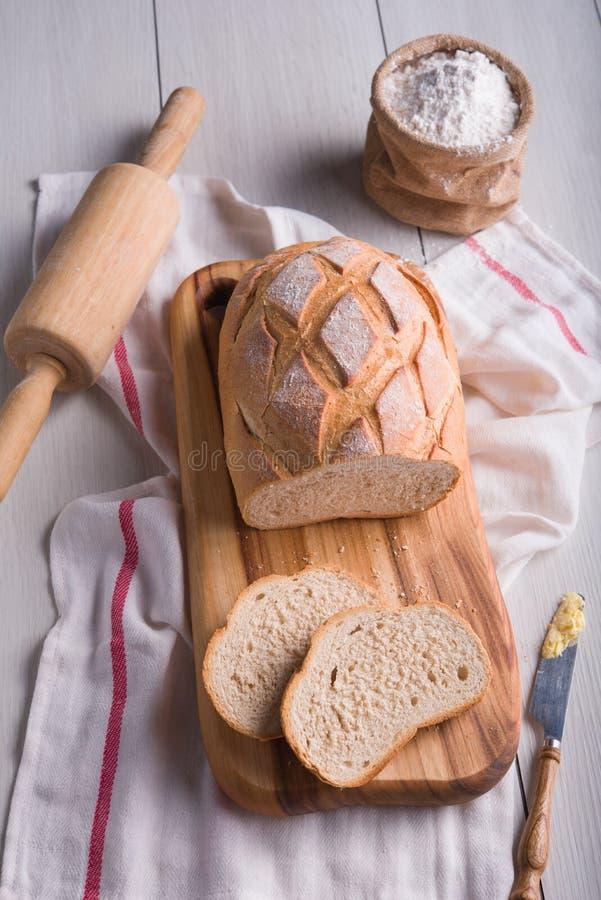 Pão recentemente cozido na placa de corte de madeira imagens de stock