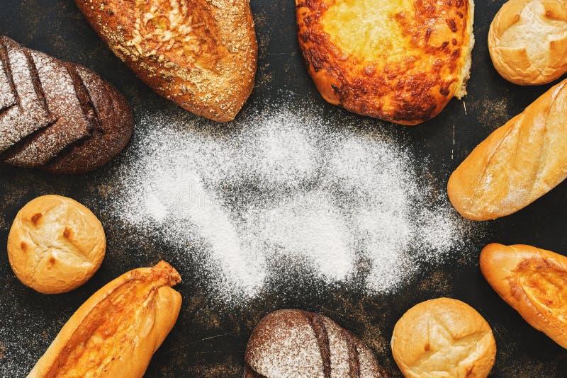 Pão variado, bolos, naco em um fundo escuro com farinha Vista superior, espaço da cópia Um grupo de vário pão caseiro fotografia de stock royalty free