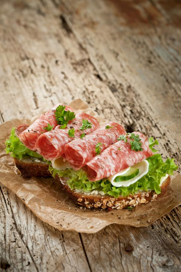 Pão Wholegrain com as sementes cobertas com a salsicha italiana picante e a salada do salame em uma placa de madeira rústica do g imagens de stock royalty free