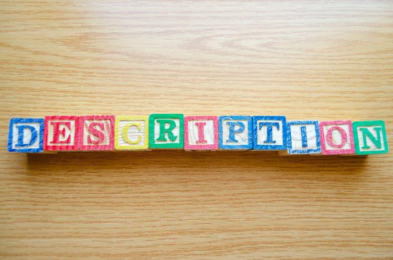 Pädagogische Spielzeugwürfel mit den Buchstaben organisiert, um Wort BESCHREIBUNG anzuzeigen - Redigieren von Metadaten und von S stockbilder