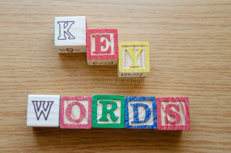 Pädagogische Spielzeugwürfel mit den Buchstaben organisiert, um Wort SCHLÜSSELWÖRTER anzuzeigen - Redigieren von Metadaten und vo lizenzfreie stockfotografie