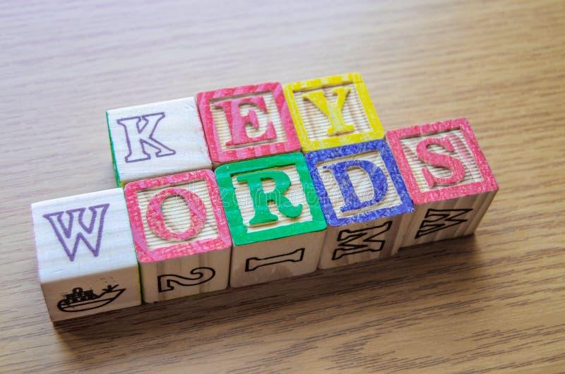 Pädagogische Spielzeugwürfel mit den Buchstaben organisiert, um Wort SCHLÜSSELWÖRTER anzuzeigen - Redigieren von Metadaten und vo lizenzfreie stockfotos