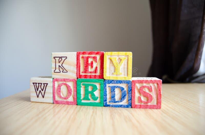 Pädagogische Spielzeugwürfel mit den Buchstaben organisiert, um Wort SCHLÜSSELWÖRTER anzuzeigen - Redigieren von Metadaten und vo lizenzfreies stockbild