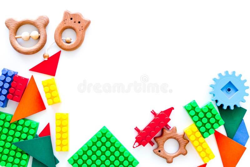 Pädagogisches Kinderspielwarenmodell Plastik-lego Blöcke und Geklapper auf weißem Draufsicht-Kopienraum des Hintergrundes lizenzfreie stockbilder