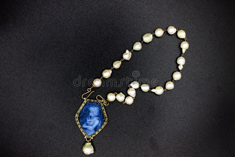 Pärlahalsbandet med den blåa korallhängen kallade också kamén som visar en värdig kvinna arkivbilder