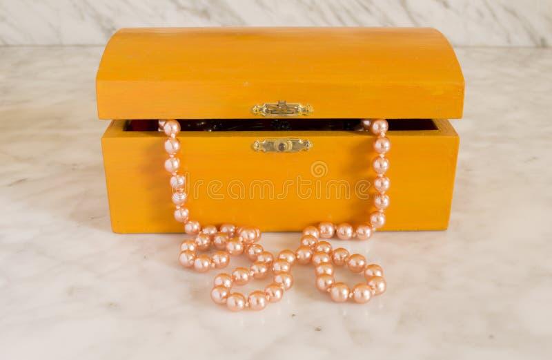 Pärlemorfärg halsband i en gammal orange kista royaltyfri fotografi