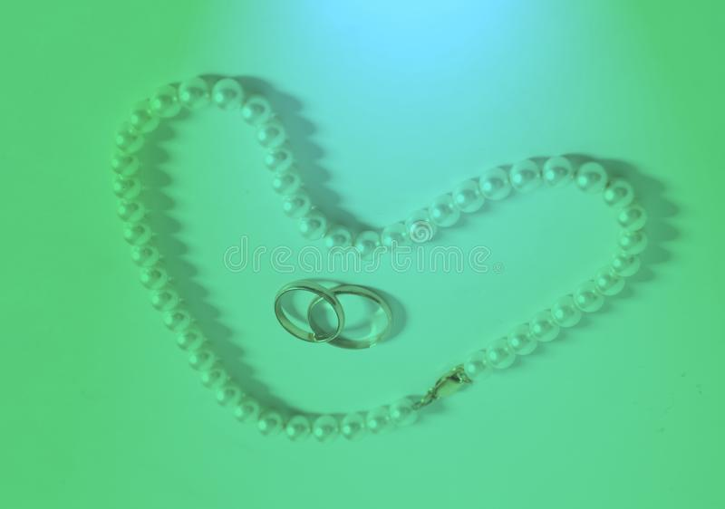 Pärlemorfärg halsband i vigselringar för hjärtaformslut fotografering för bildbyråer