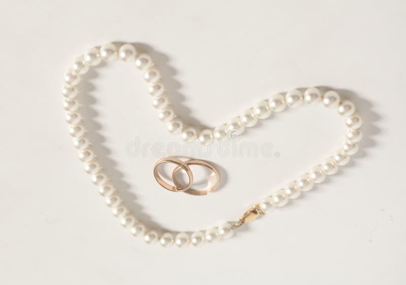 Pärlemorfärg halsband i vigselringar för hjärtaformslut arkivbilder