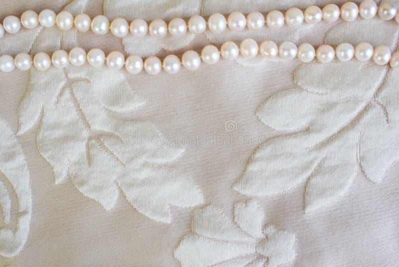 Pärlemorfärg halsband på bakgrund för satängtygtextur med utrymme för royaltyfria foton