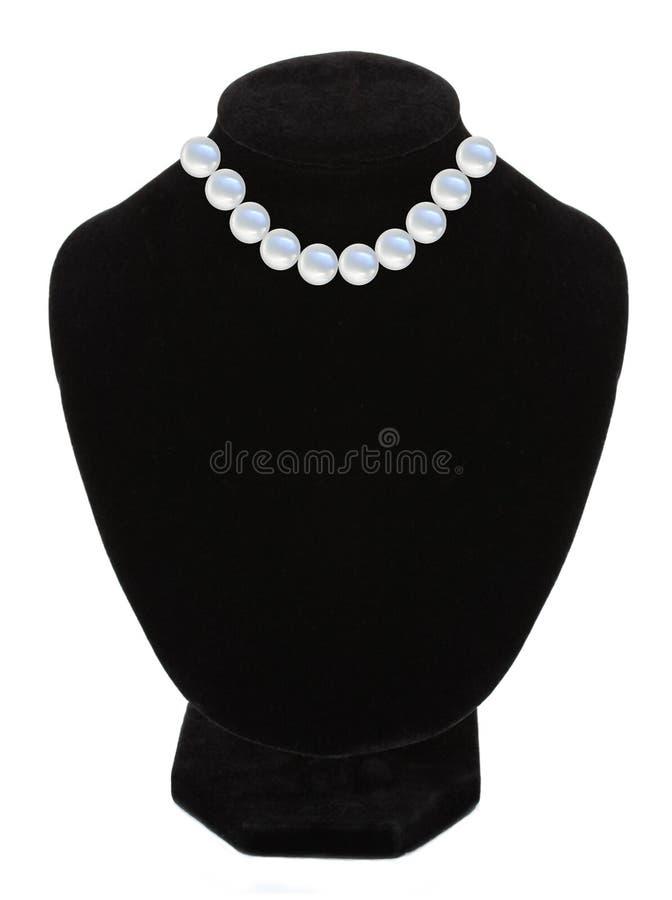 Pärlemorfärg halsband på den svarta skyltdockan som isoleras över vit royaltyfria foton