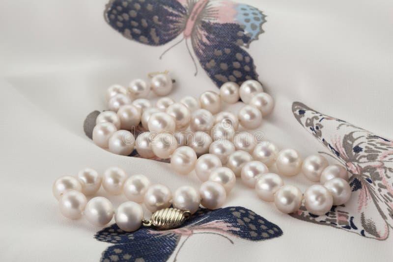 Pärlemorfärg halsband på pastellfärgad och vit fjärilskvinnas överkant arkivbild