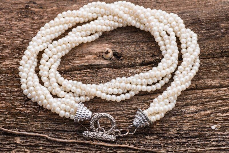 Pärlemorfärg halsband på wood bakgrund royaltyfri fotografi