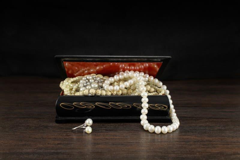Pärlor i öppen bröstkorg för gamla smycken, halsband för tappningskattask och pärla Inskriften av r?tt f?rgar lokaliserat ?ver te arkivbilder