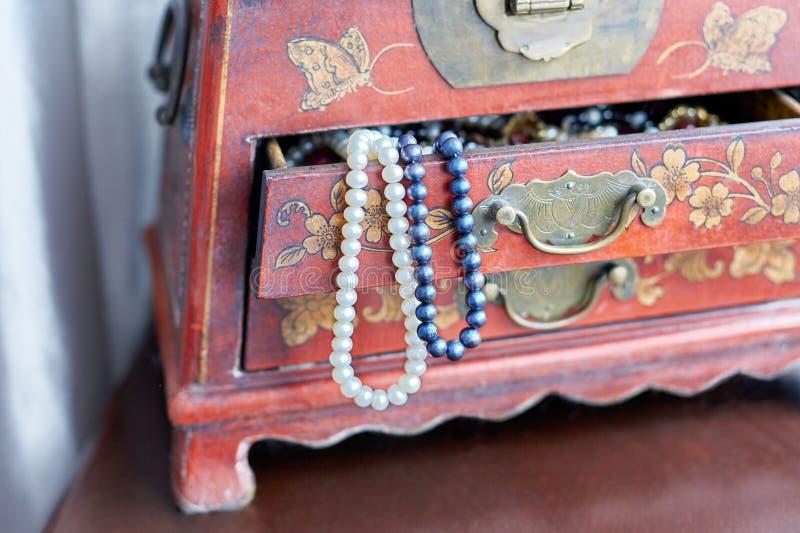Pärlor i en ask Två vita halsband och lila pärlor i öppnat tappningfall med härliga prydnader på träyttersida royaltyfri foto