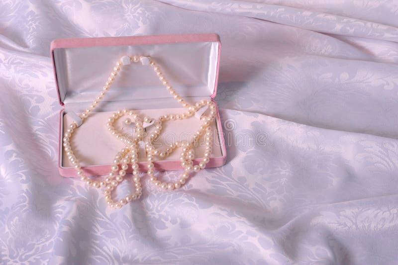 Pärlor i rosa väska arkivbilder