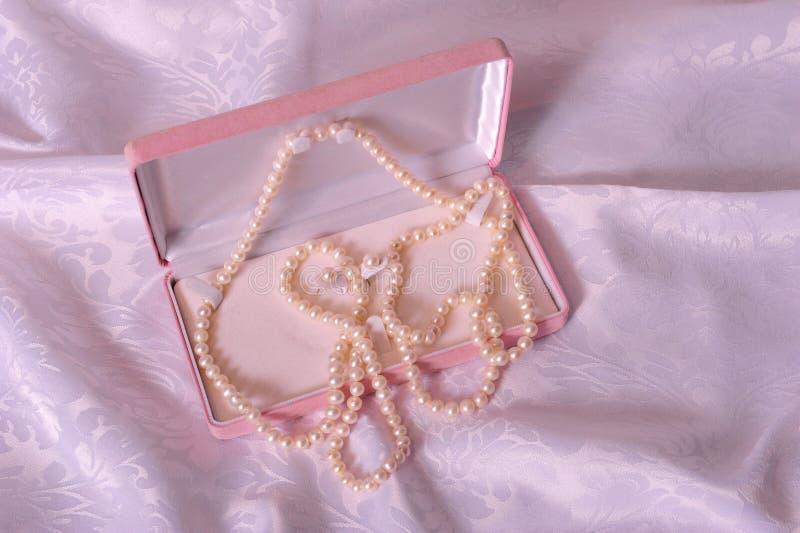 Pärlor i rosa väska royaltyfria foton