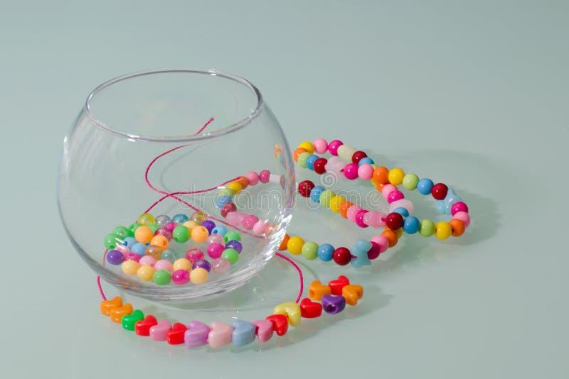 Pärlor, smycken och tillbehör i en exponeringsglasvas på en turkosbakgrund Handarbete med barn arkivbilder