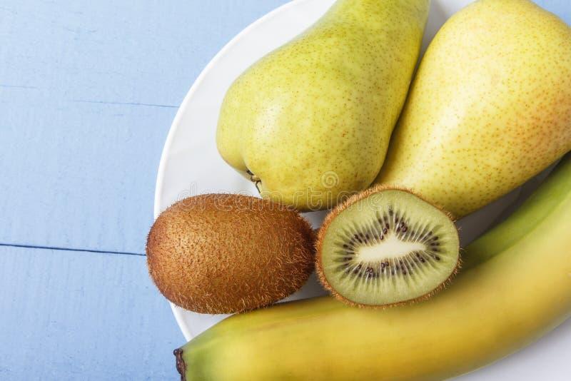 Päron, banan och kiwi på träbakgrund med kopieringsutrymme Ingredienser för diet- och sund frukost eller matställe överkant VI royaltyfria foton