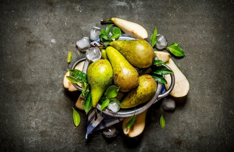 Päron i en kastrull med sidor och is fotografering för bildbyråer
