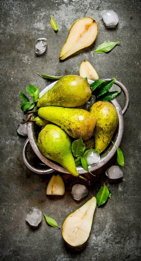 Päron i en kastrull med sidor och is arkivfoto