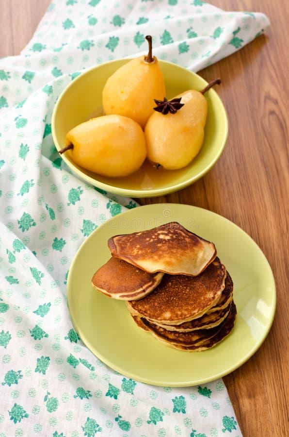 Päron som låtas småkoka i citrus fruktsaft och pannkakor royaltyfria foton