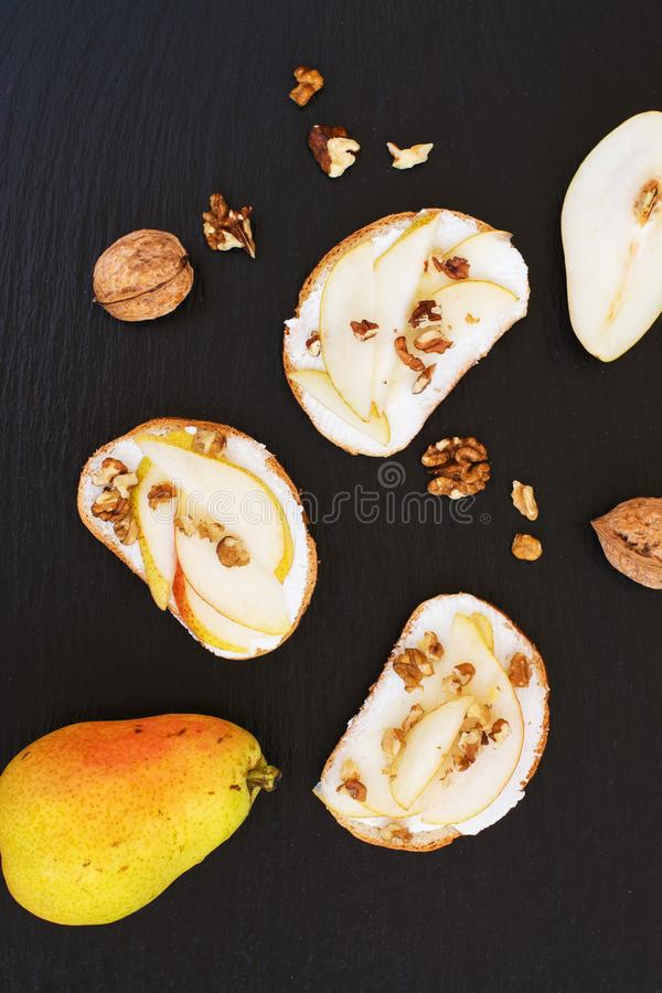Päronbruschetta med gräddost, muttrar och honung royaltyfri fotografi