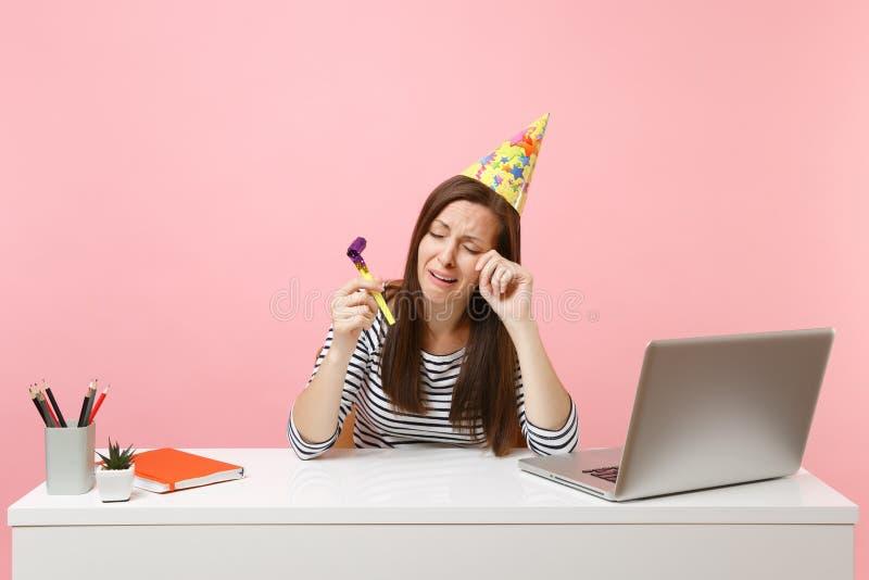 Płacz kobieta w przyjęcie urodzinowe kapeluszu z bawić się fajczanej odświętności obcierania samotne łzy podczas gdy siedzi pracę fotografia stock