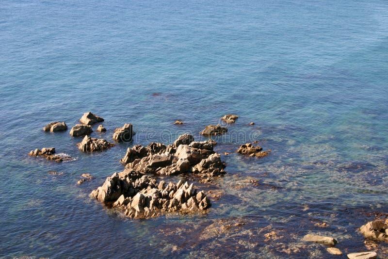 Płytka błękitne wody skalisty seashore zdjęcia stock